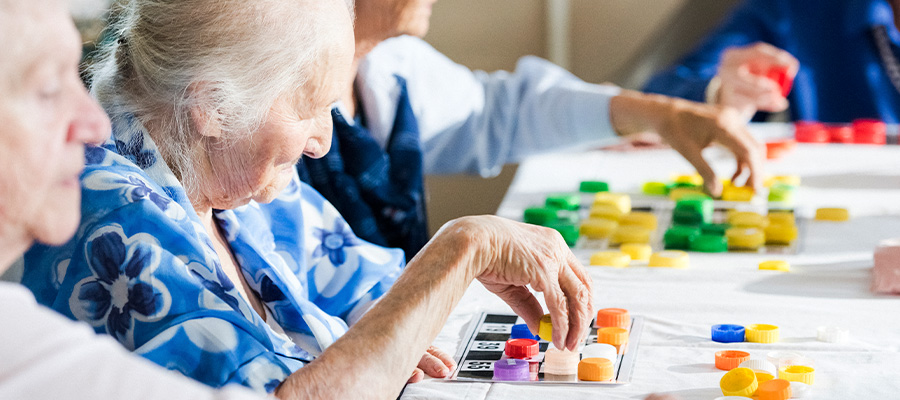 Senior citizens play bingo with colorful pieces