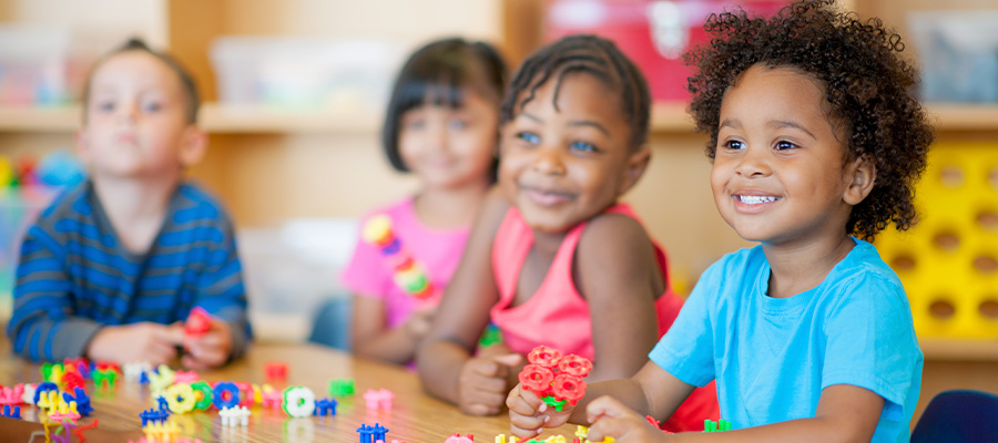 Four young children sit around a table with colorful toys