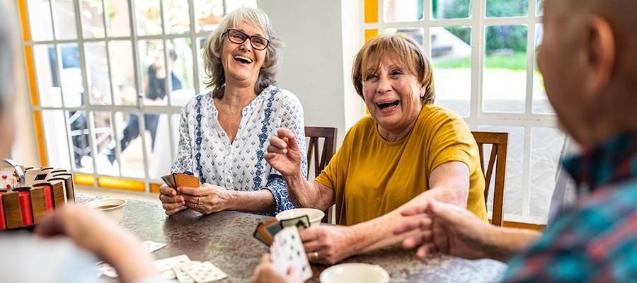 Senior citizens laugh while playing cards